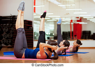 Working on those abs - Group of young women working out and...