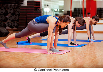 Concentrating during yoga class - Pretty Latin women trying...