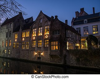 House decorated with Christmas stars along canal at night in...