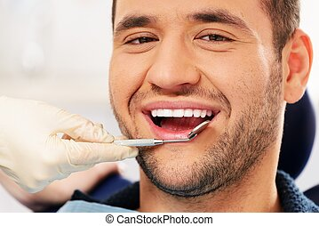 Happy man doing teeth checkup at dentists surgery