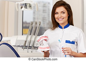 Young beautiful brunette woman dentist with plastic jaw...