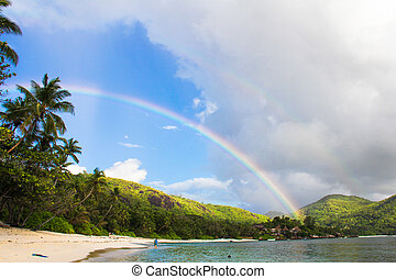 Rainbow over tropical island and white beach at Seychelles