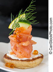 Single Blini appetizer with smoked salmon and caviar, garnished with dill. Close-up view
