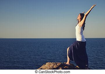 Greeting the blue - Beautiful young woman standing on a rock...