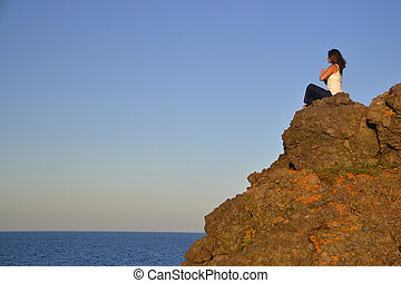 Namaste - Beautiful young woman sitting on a rock...