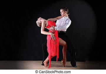 Latino dancers in ballroom against on black