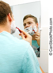 young man shaving his face, reflection in mirror