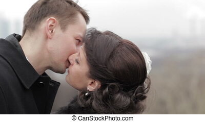 Bridal pair kissing. - Bride and groom kissing outdoors....