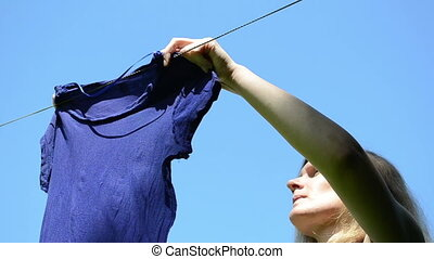 woman hang laundry - Woman hanging laundry on clothesline...