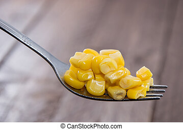 Corn on a Fork on wooden background