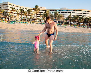 Happy family: dad and child on beach in Persian Gulf ,Dubai...