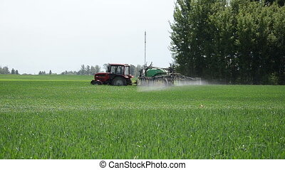 tractor sprinkler spraying small streams fertilizers on crop...