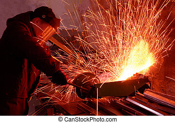 worker white hot sparks at grinding steel material