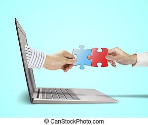 Hand holding puzzle coming out from screen connect with another