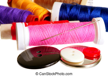 Sewing Stuff - Thread rolls, buttons and needle on a white...