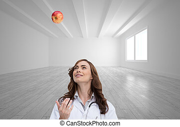 Composite image of happy doctor throwing apple - Composite...