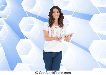 Composite image of smiling casual brunette using her tablet pc