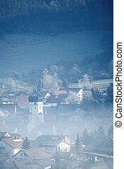 Village in winter fog