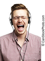 Listening to music and singing with headphones - Young man...