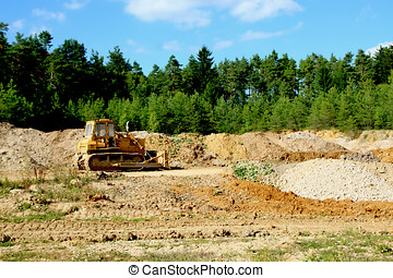 Excavator on mound and forest background