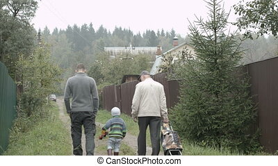 Two men and a boy walking in the countryside.