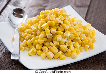Plate with Corn on wooden background