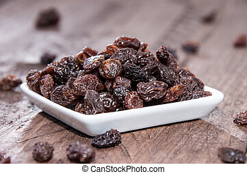 Small plate with Raisins on wooden background
