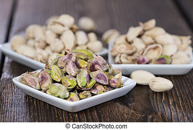 Pistachios in a bowl (on wood) - Pistachios in a bowl on...