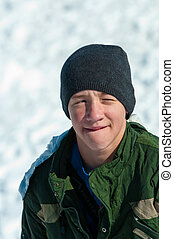 teen sitting in snow - Handsome teen in snow, squinting from...
