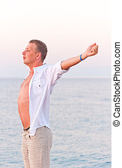 bare-chested man stretching on sea background