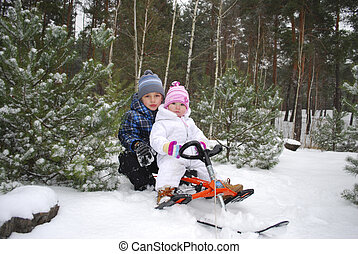 In the forest, the boy with a little girl sitting on a sled.