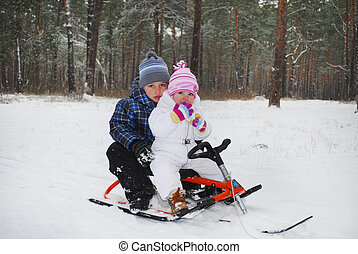 the boy with a little girl sitting on a sled.