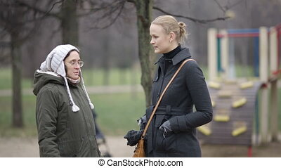 Women talking - Two women talking outdoor Friends or...