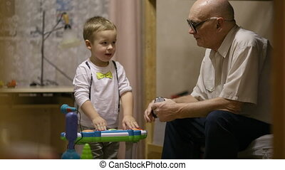 Grandfather and childred playing - Grandfather sitting and...