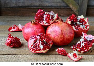 ripe pomegranates on a rustic table, food closeup
