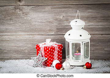 Burning lantern in the snow with christmas decoration, on...