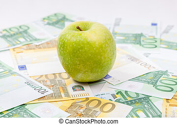 Green apple on Euro banknotes spreaded over the floor -...