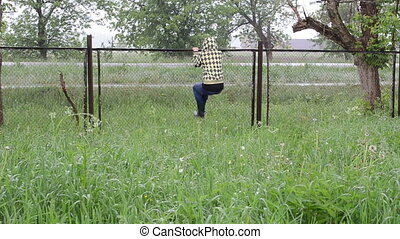 woman climb fence rain - Hurry woman girl with jacket and...