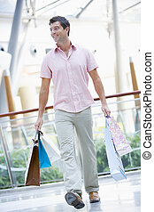 Man with shopping bags at a shopping mall