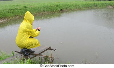 woman feed fish rain - Woman with water proof coat on small...