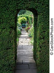 Yew arch, English garden - Pretty flagstone path through...
