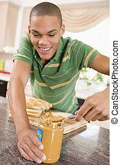 Teenage Male Making Peanut Butter Sandwich