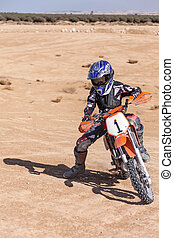 teenager on a motorbike through the desert terrain, summer...