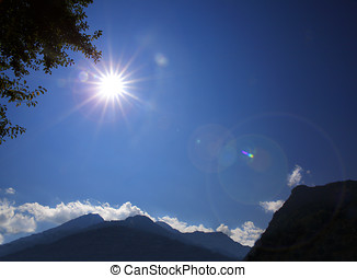 Shining sun on blue sky in the mountains
