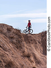 rider on the bike before the obstacle in the wilderness, in...