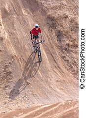 rider on a bike, with a steep hill, summer day