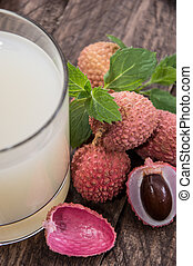 Lychee Juice with fresh fruits on wooden background