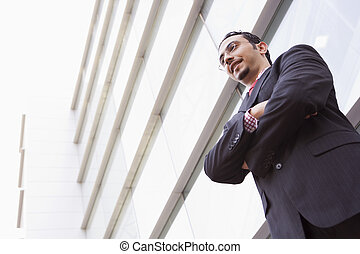 Businessman standing outdoors by building smiling high...