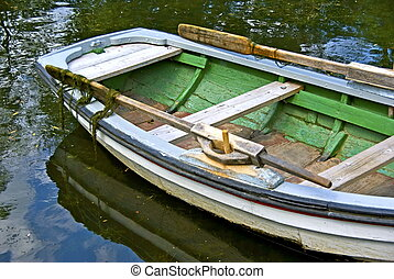 Rowing boat - Old wooden rowing boat for hire at a pond.