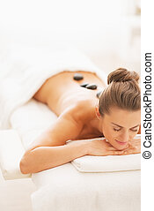 Relaxed young woman receiving hot stone massage